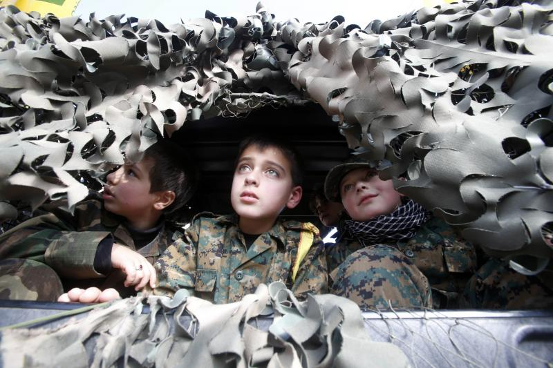 Children look on from inside a military vehicle during the funeral of Lebanon's Hezbollah commander Mohamad Issa