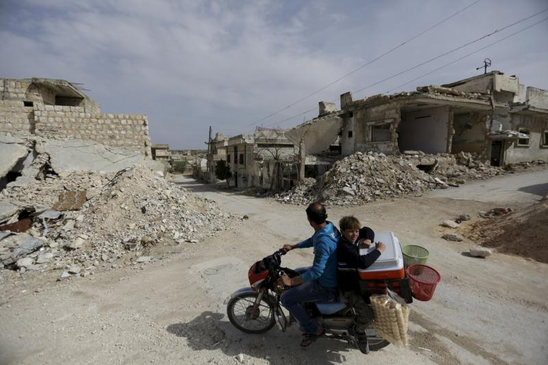 A man and a boy drive a motorbike while selling ice-cream in the town of Marat Numan in Idlib province, Syria, Syria, March 19, 2016.