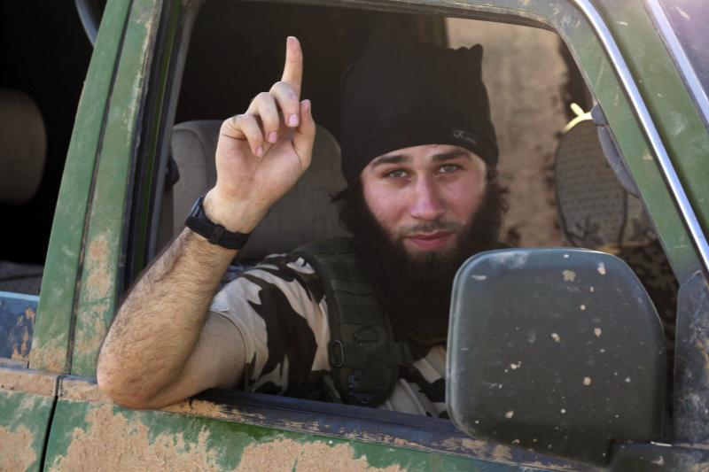 An Islamic State fighter gestures from a vehicle in the countryside of the Syrian Kurdish town of Kobani, after the Islamic State fighters took control of the area, October 7, 2014.