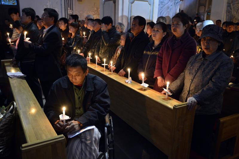 Worshippers hold candles on the eve of Easter, at a Catholic church in Taiyuan, Shanxi province, March 2013.
