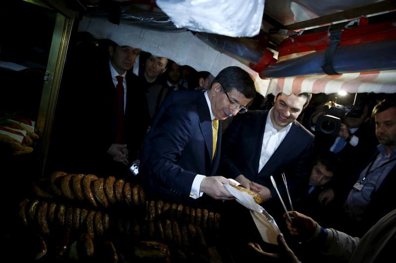 Turkish Prime Minister Ahmet Davutogluand his Greek counterpart Alexis Tsipras buy simit, traditional sesame bread, during a sightseeing tour in the Aegean port city of Izmir, western Turkey, March 8, 2016.