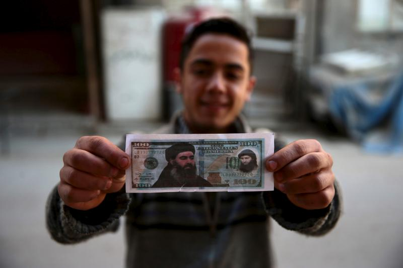 A boy poses while showing one of the fake U.S. 100 dollar banknotes depicting Islamic State's leader Abu Bakr al-Baghdadi (L) and al-Nusra Front's leader Abu Mohammed al-Joulani (R), Syria December 27, 2015.