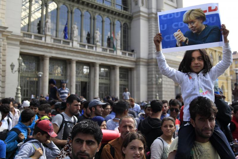 A young girl holds up a picture of Angela Merkel as migrants set off on foot for the border with Austria from Budapest, September 2015.