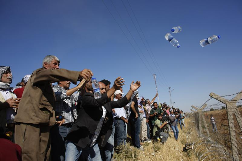 Turkish Kurds throw water bottles to the Syrian side over the Turkish-Syrian border fence, near the southeastern town of Suruc in Sanliurfa province September 26, 2014.