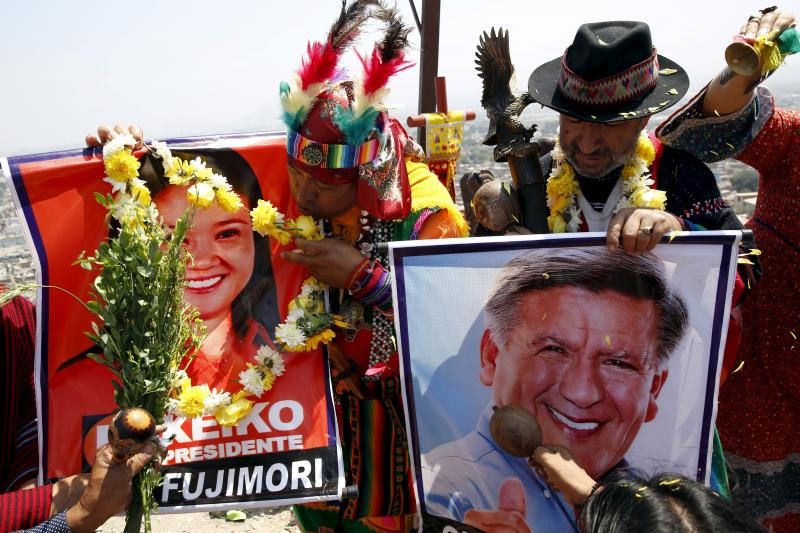 Peruvian shamans holding posters of Peru's presidential candidates Keiko Fujimori and Cesar Acuna perform a ritual of predictions for the new year at Morro Solar hill in Chorrillos, Lima, Peru, December 29, 2015.