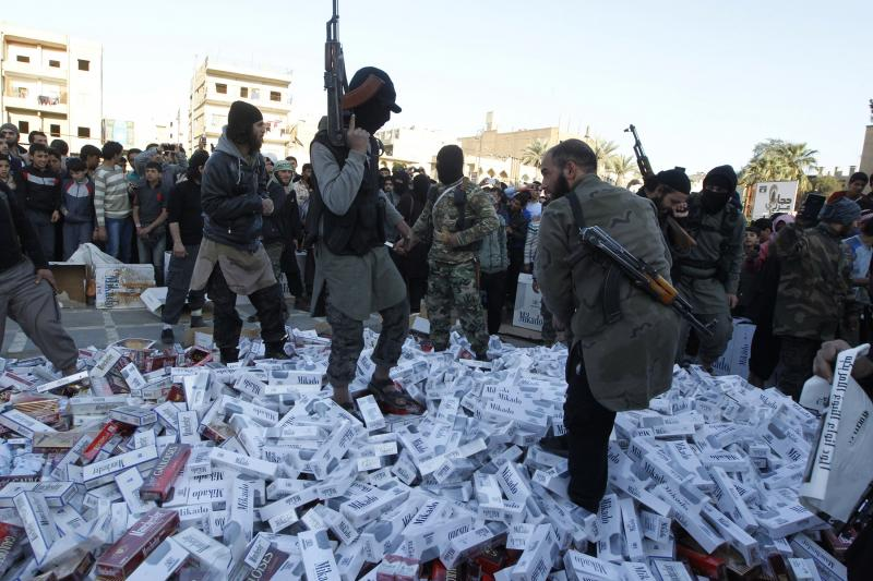 Fighters from Islamic State ISIS hold their weapons as they stand on confiscated cigarettes before setting them on fire in the city of Raqqa, April 2, 2014.