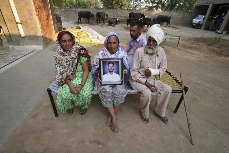 Malkit Kaur, mother of Kuldeep Singh, a cotton farmer who committed suicide, holds his portrait as Kuldeep's father Thana Singh (R), his brother Hardeep Singh (2nd R) and his widow Bhinder Kaur (L) sit on a cot at their residence on the outskirts of Bhati