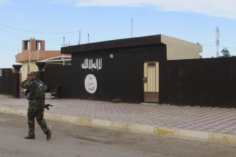 An Iraqi Shi'ite fighter walks past walls painted with the ISIS flag, November 24, 2014.