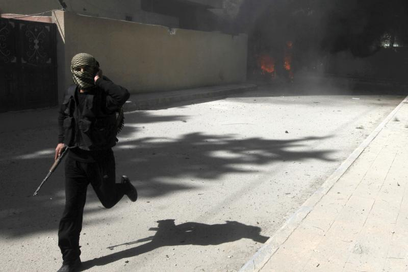 A fighter from al-Qaeda aligned rebel group Jabhat al-Nusra runs with his weapon as their base is shelled in Raqqa province, eastern Syria, March 14, 2013.