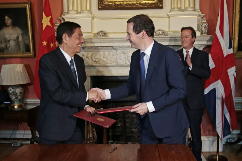 Britain's Chancellor Geroge Osborne and China's Yu Guangzhou shake hands after signing an agreement at Number 10 Downing Street in London, October 2015.