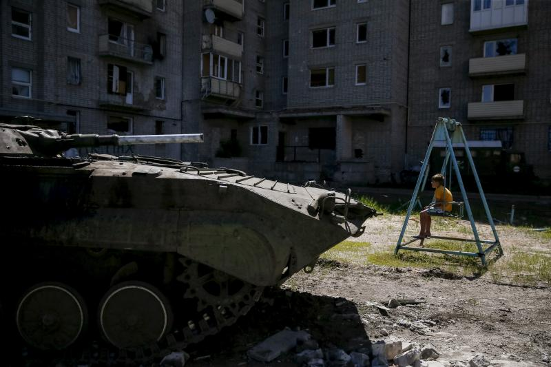 A Ukrainian armored personnel carrier near Donetsk in front of a building damaged during fighting between the Ukrainian army and pro-Russian separatists, eastern Ukraine, June 2015.