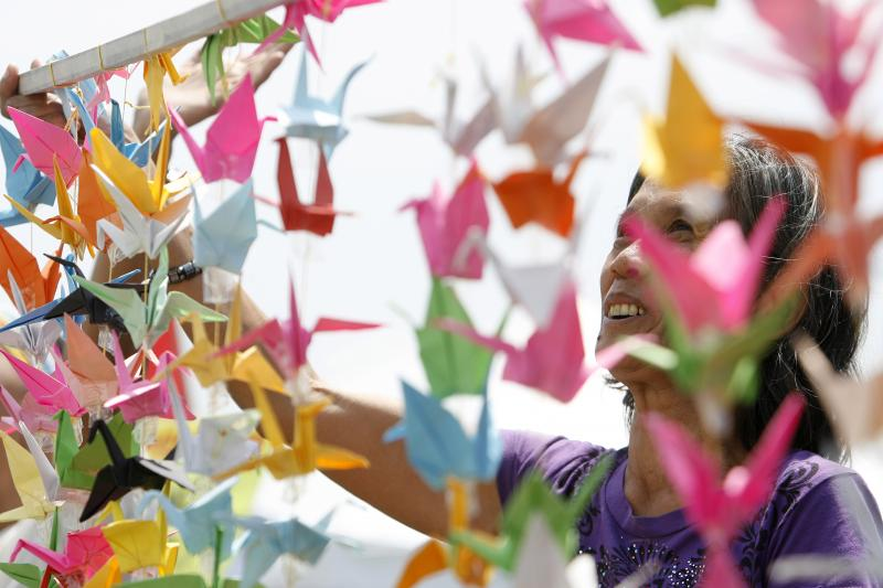 A member of a Philippine solidarity group waves Japanese paper cranes while welcoming the arrival of the SS Oceanic cruise ship from Japan at the port of Manila, April 13, 2011.