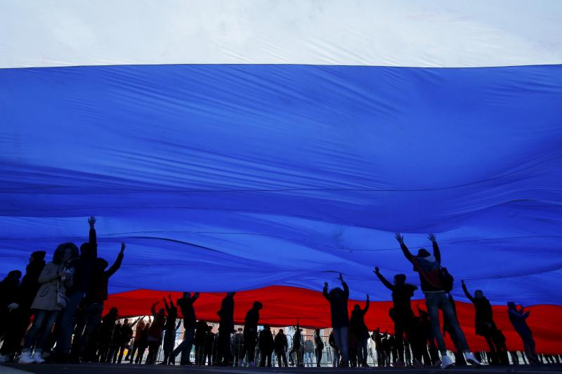 People hold a giant Russian national flag to mark the second anniversary of Russia's annexation of the Crimea region, in Moscow, March 2016.