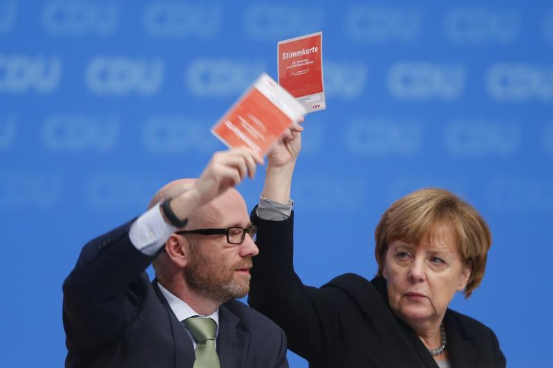 Germany's Christian Democratic Union secretary general Peter Tauber and German Chancellor and leader of the CDU Angela Merkel vote on a resolution about refugees at the CDU party congress in Karlsruhe, Germany, December 2015.