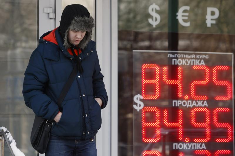A man walks near a board showing currency exchange rates of the U.S. dollar against the rouble in Moscow, January 2016.