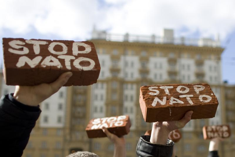"""Members of the Kremlin-loyal youth organisation """"Young Russia"""" hold up bricks during an anti-NATO protest in front of the U.S. embassy in Moscow, April 2009."""