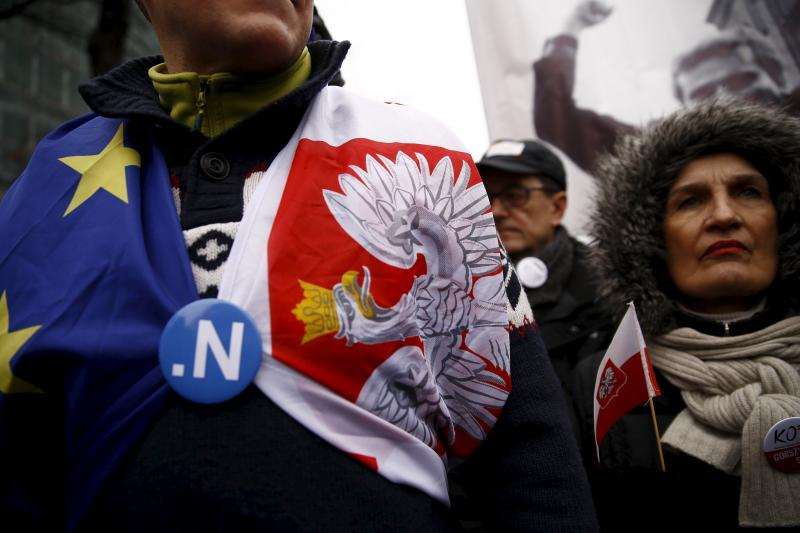 A man covered with EU and Polish flag takes part in a march demanding their government to respect the country's constitution, in front of the Constitutional Court in Warsaw, Poland, March 12, 2016.