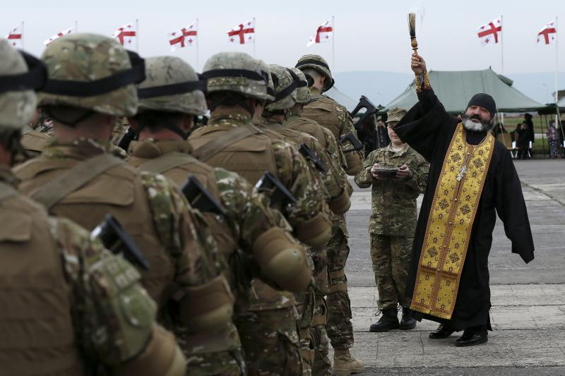 A priest blesses servicemen during a farewell ceremony at the Vaziani military base outside Tbilisi, March 24, 2015.