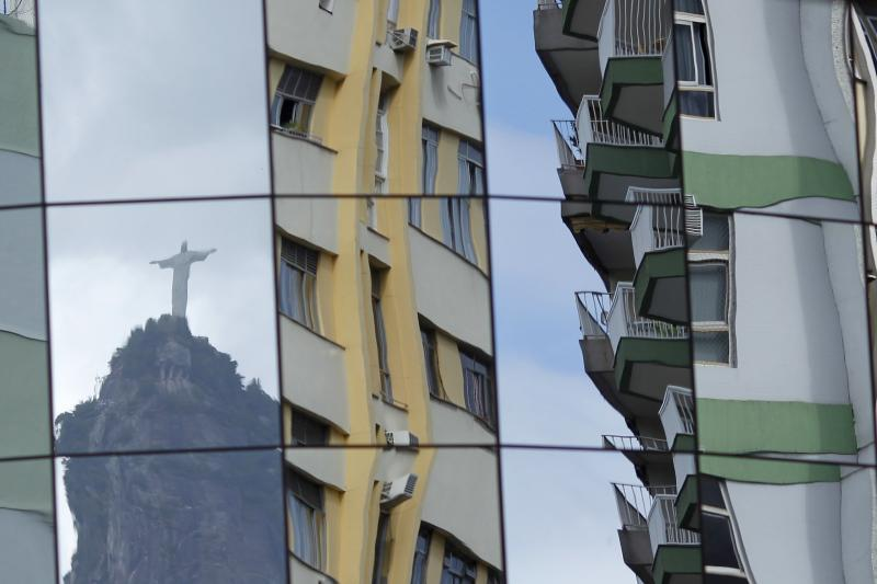 """Rio de Janeiro's famous """"Christ the Redeemer"""" statue is reflected on the glass facade of a building in Botafogo in Rio de Janeiro, February 25, 2011."""