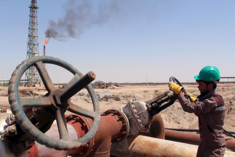 A worker checks the valve of an oil pipe at Al-Sheiba oil refinery in the southern Iraq city of Basra, April 17, 2016.
