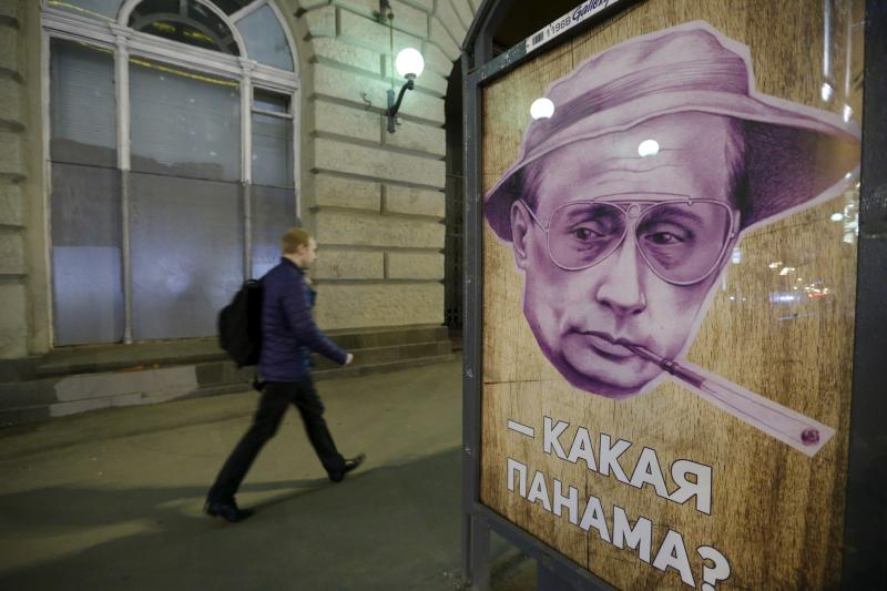 """A man walks past a poster depicting Russian President Vladimir Putin and reading """"Which Panama?"""" at a bus stop in Moscow, Russia, April 6, 2016."""