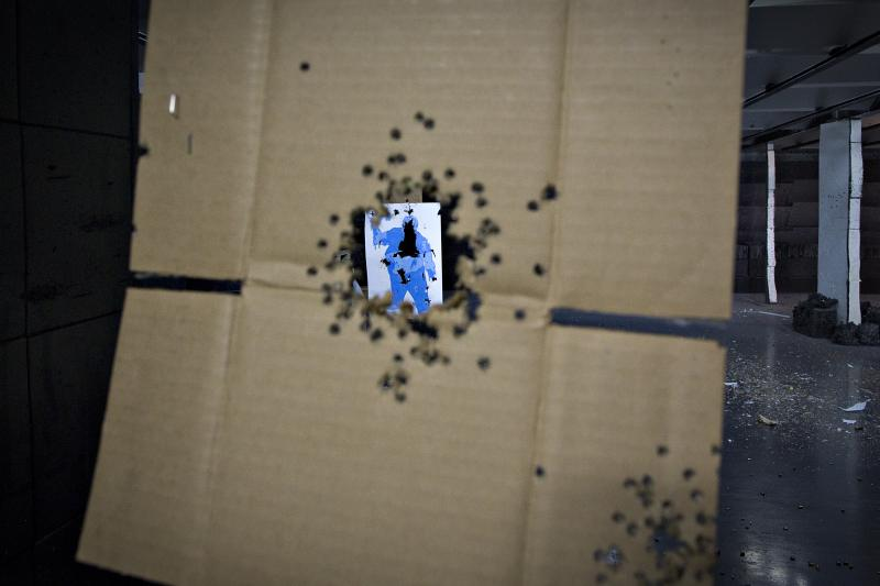 A target hit several times is seen through a piece of cardboard also peppered with bullet holes at the DVC Indoor Shooting Centre in Port Coquitlam, British Columbia March 22, 2013.