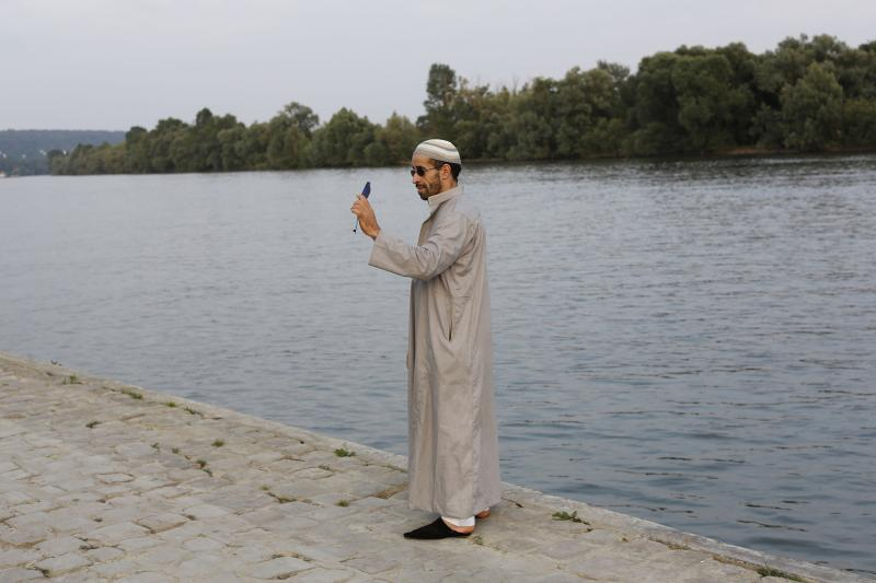 A Moroccan Muslim takes a photograph of himself in Mantes-la-Jolie, a suburb of Paris, July 2013.