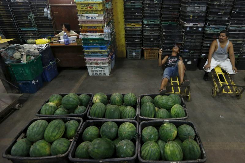 Workers take a break from unloading watermelon at a wholesale market in Kuala Lumpur, Malaysia, January 7, 2016.