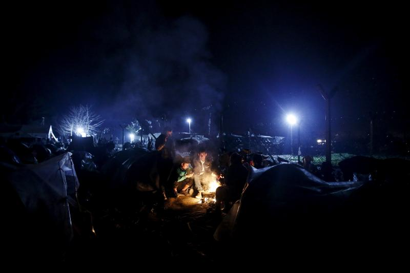 A Syrian refugee family gathers around a bonfire next to the Greek-Macedonian border fence, at a makeshift camp near Idomeni, Greece, March 2016. Picture taken March 16. Europe's response to the refugee crisis has failed.
