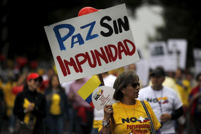 Demonstrators protest against the Revolutionary Armed Forces of Colombia (FARC) as they ask for changes to a peace agreement between FARC and President Juan Manuel Santos' government in Bogota, Colombia, April 2016. The sign reads 'Peace without impunity'