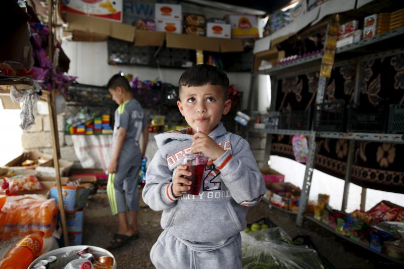 Yazidi boy Emad, 5, and his brother Murad (back), who was trained by Islamic State, stand in a grocery at a refugee camp near the northern Iraqi city of Duhok, April 19, 2016.