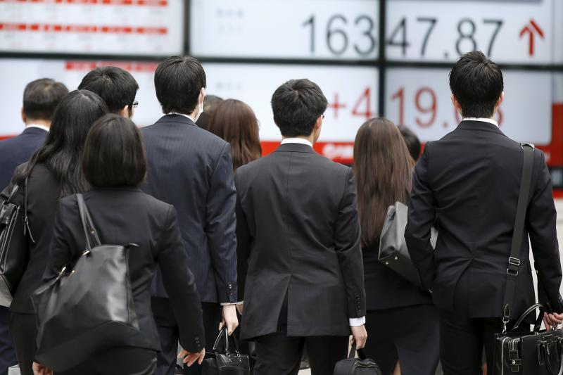 People walk in front of an electronic board showing Japan's Nikkei average outside a brokerage in Tokyo, April 2016. Shinzo Abe faces a major economic challenge.