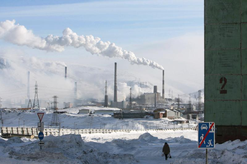 A woman walks near a nickel mine in the arctic city of Norilsk April 3, 2007.