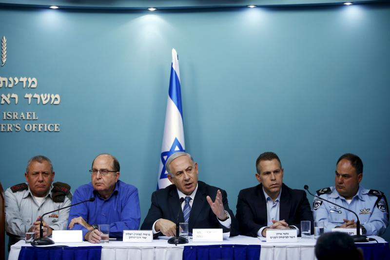 Israel's Prime Minister Benjamin Netanyahu sits next to Defense Minister Moshe Yaalon (2nd L), Army Chief of Staff Lieutenant-General Gadi Eisenkot (L), acting Police Commissioner Bentzi Sau (R) and Public Security Minister Gilad Erdan (2nd R), as he spea