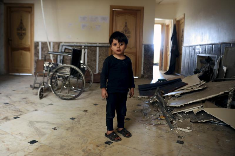 A boy, who was evacuated with others from two rebel-besieged towns of Foua and Kefraya in the northwestern province of Idlib, is seen standing inside a hospital that was struck by an explosion on the outskirts of the Sayeda Zeinab district south of Damasc