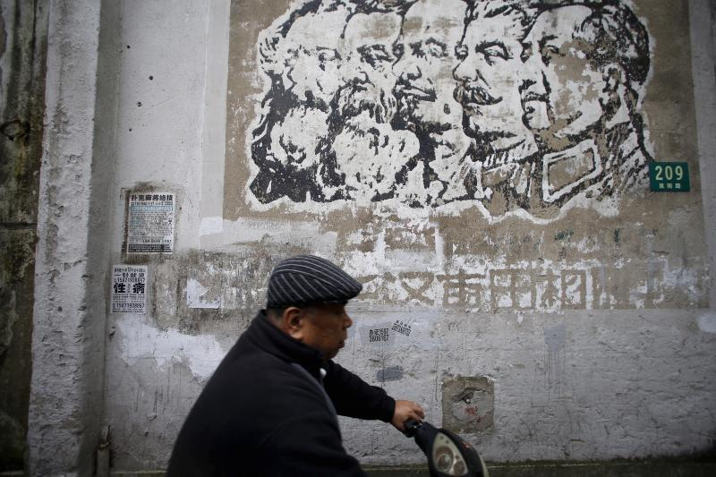 A man rides a electric bicycle past a Cultural Revolution–era poster in Shanghai, April 2016. May 16 marks the fiftieth anniversary of the beginning of the Cultural Revolution.