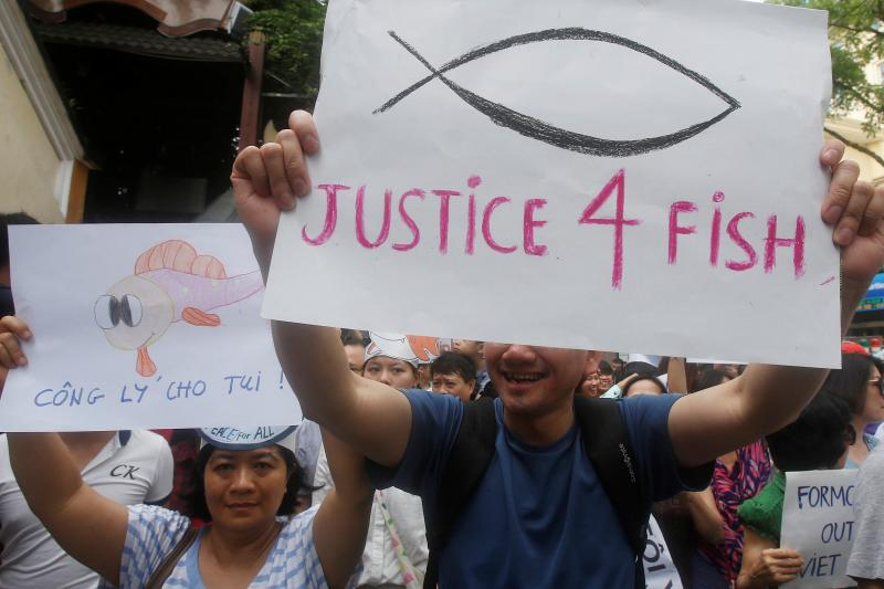 Demonstrators, holding signs, say they are demanding cleaner waters in the central regions after mass fish deaths in recent weeks, in Hanoi, Vietnam May 1, 2016.