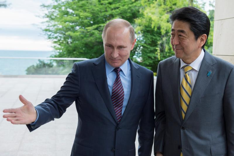 Russian President Vladimir Putin shows Japanese Prime Minister Shinzo Abe the way during a meeting at the Bocharov Ruchei state residence in Sochi, Russia, May 6, 2016.