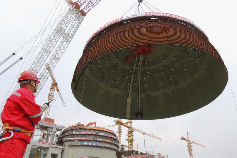 A worker looks on as the dome roof of a generator unit is lifted to be installed, at Tianwan Nuclear Power Plant, in Lianyungang, Jiangsu province, China, September 26, 2015.