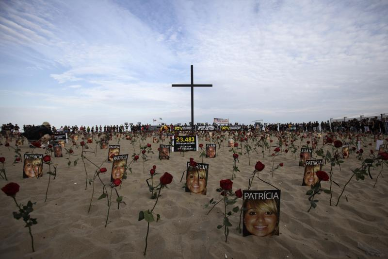 Flowers and pictures of victims of street violence are placed on Copacabana beach in Rio de Janeiro July 31, 2011.