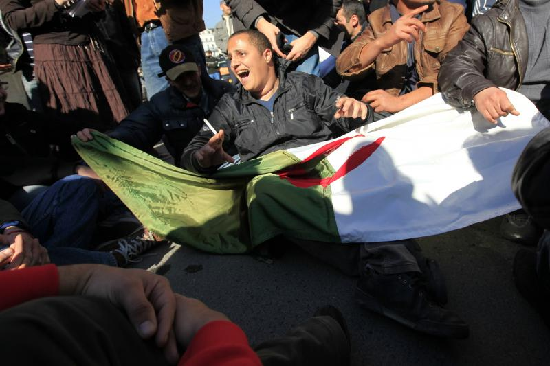 Unemployed Algerians hold a Algerian national flag as they protest outside the employment ministry building in Algiers, February 2011.