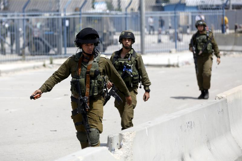 An Israeli soldier prepares to throw a stun grenade towards Palestinian journalists near the scene where a Palestinian woman and a man were shot dead by Israeli police near Qalandia checkpoint near the West Bank city of Ramallah, April 2016.