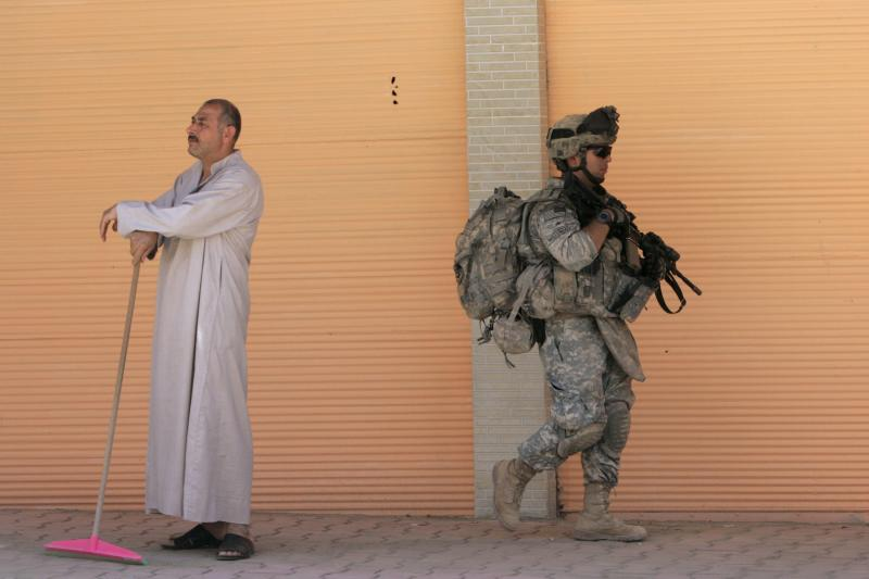 A U.S. soldier walks past a resident during a patrol in Samarra, Iraq, June 2009.
