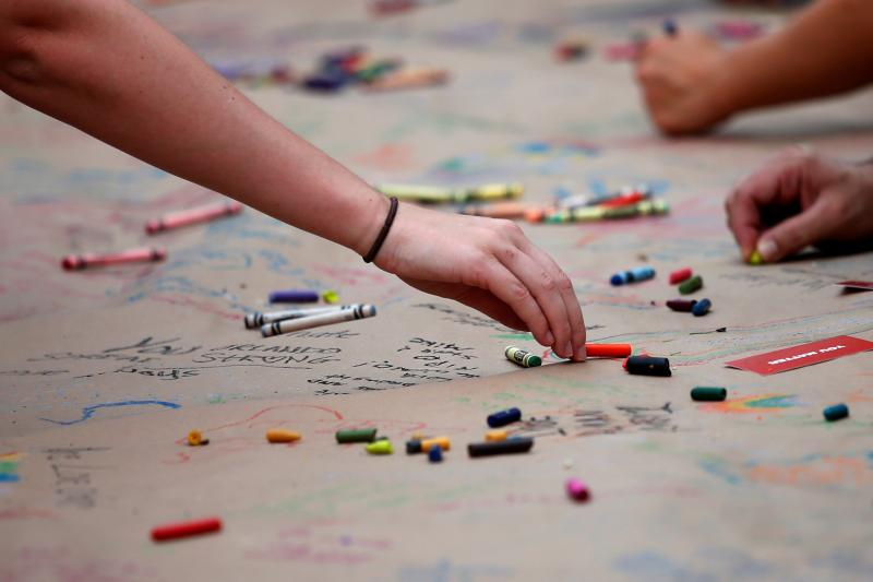 Well wishers use crayons to leave messages for the deceased ahead of a candle light vigil in memory of victims one day after a mass shooting at the Pulse gay night club in Orlando, Florida, June 13, 2016.