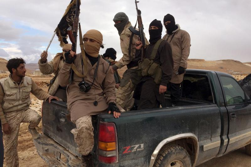 Al Qaeda-linked Nusra Front fighters carry their weapons on the back of a pick-up truck during the release of Lebanese soldiers and policemen in Arsal, eastern Bekaa Valley, Lebanon, December 1, 2015.