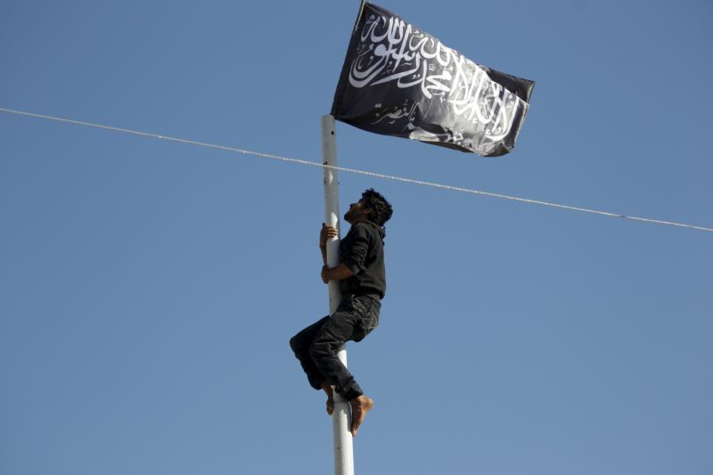 A member of al Qaeda's Nusra Front climbs a pole where a Nusra flag was raised at a central square in the northwestern city of Ariha, after a coalition of insurgent groups seized the area in Idlib province May 29, 2015.