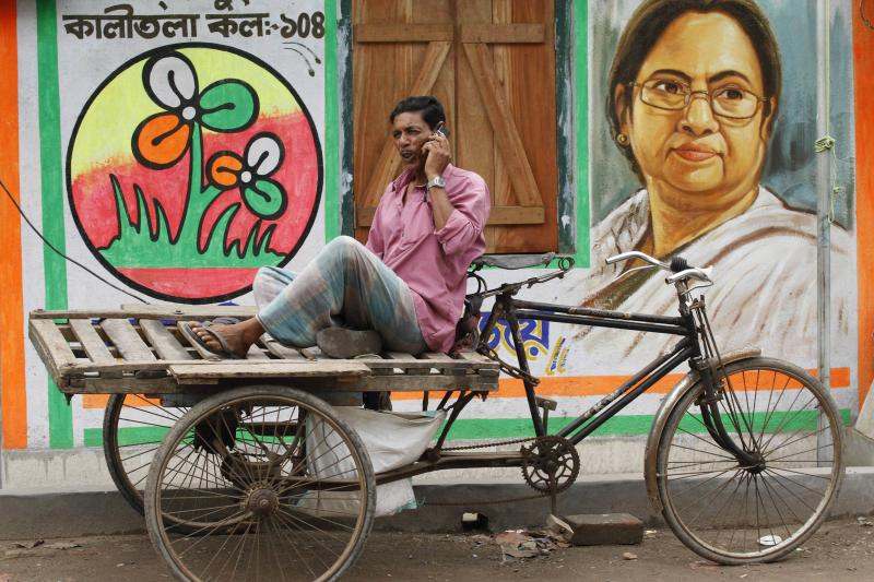 A cycle rickshaw puller sits near a wall painted with a picture of Mamata Banerjee in Kolkata, April 2011.