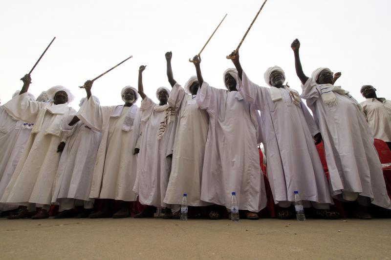 Tribal men from Darfur wave to Sudanese President Omar al-Bashir during a rally to support Darfur peace talks in Khartoum August 7, 2010.