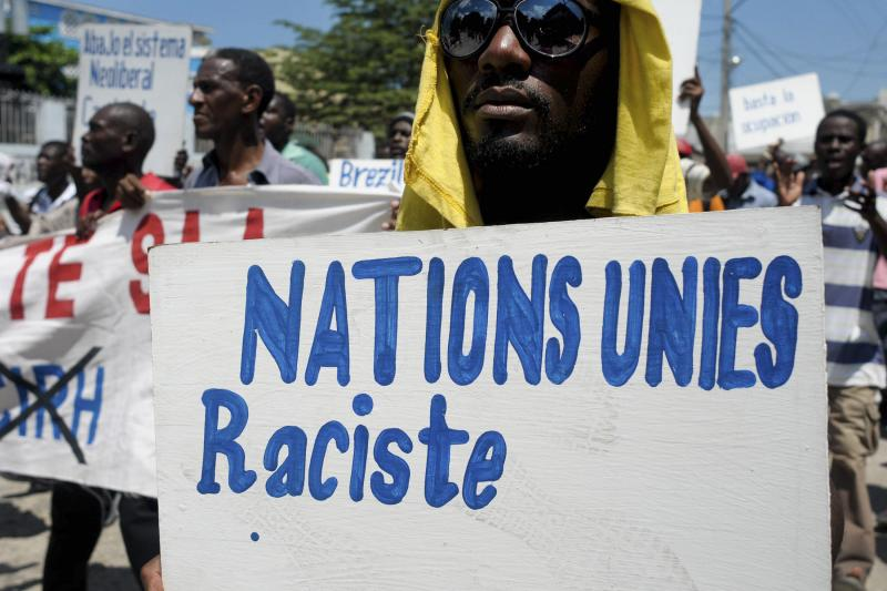 """A demonstrator carries a sign which reads """"United Nations is racist"""" during an anti-UN protest in Port-au-Prince, September 14, 2011."""