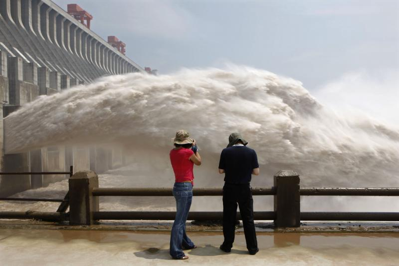 Journalists take pictures as the Three Gorges Dam discharges water to lower the level in its reservoir in Yichang, Hubei province, July 2010.